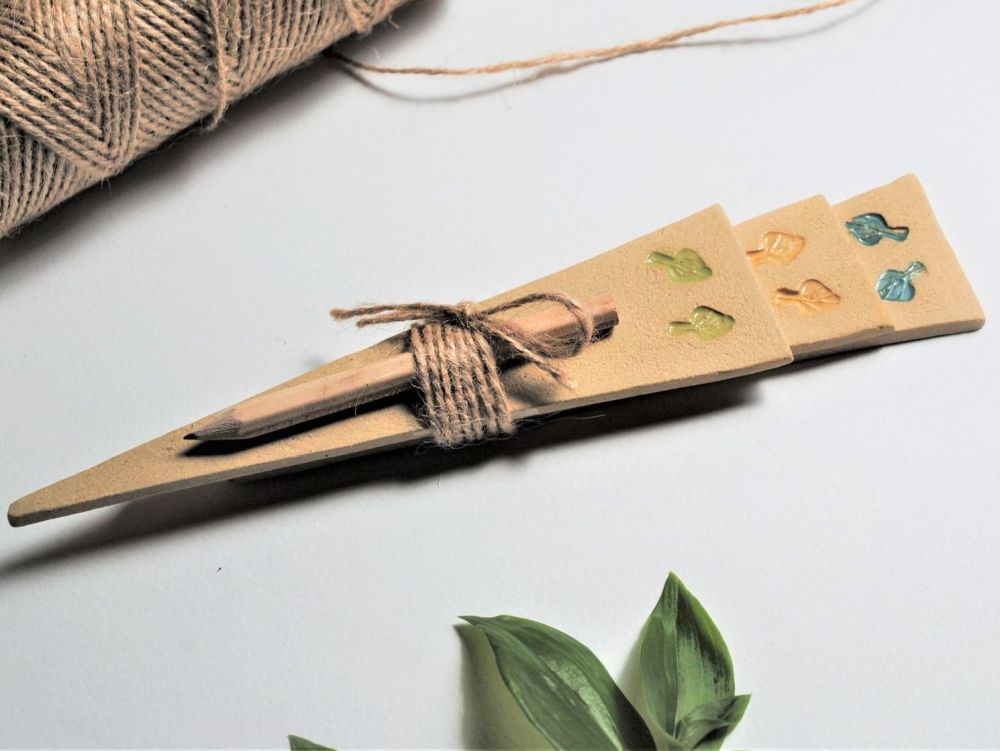 Handmade ceramic leaves plant markers with pencil.