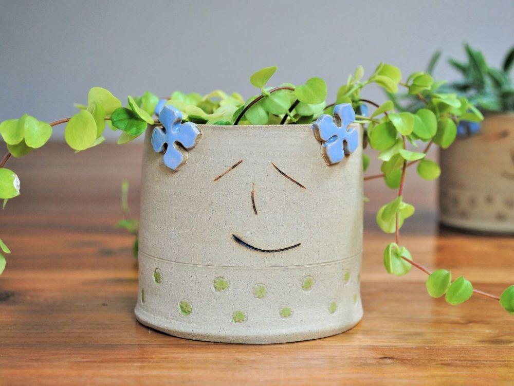 Ceramic face planter with hydrangea flower detials.