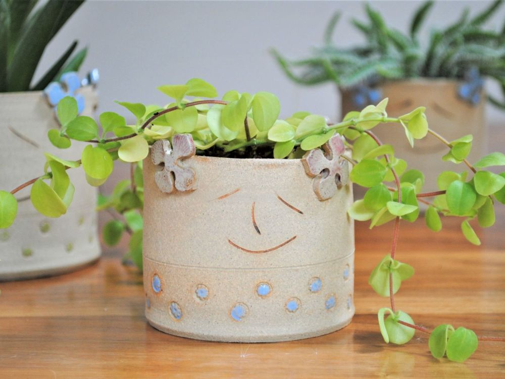 Planter decorated with pale pink Hydragena and blue flowers.