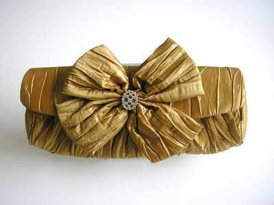 Designer evening clutch bag.metallic gold.large bow,jewel