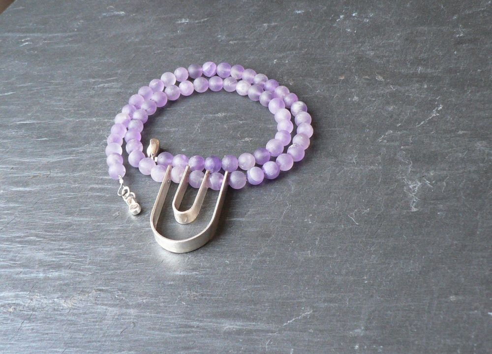 A necklace of frosted amethyst beads with a sterling silver pendant.