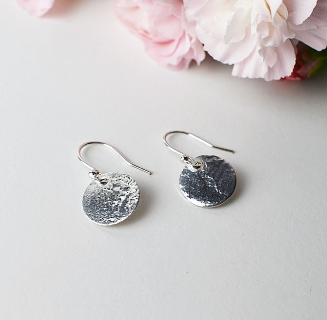 A pair of patterned disc earrings with flowers in the background