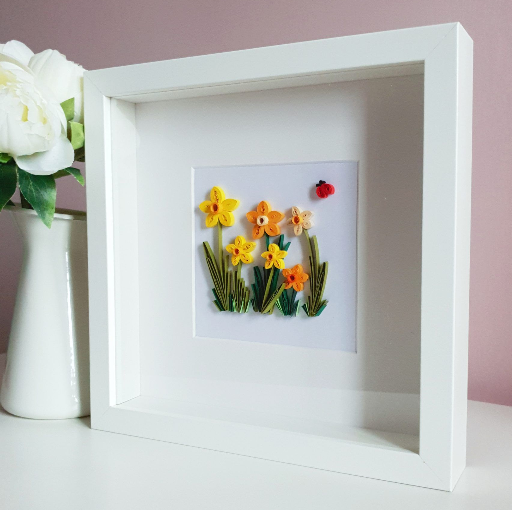 Paper daffodils in a white frame