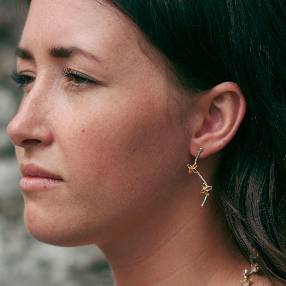 Woman wearing blossom stud drop earrings