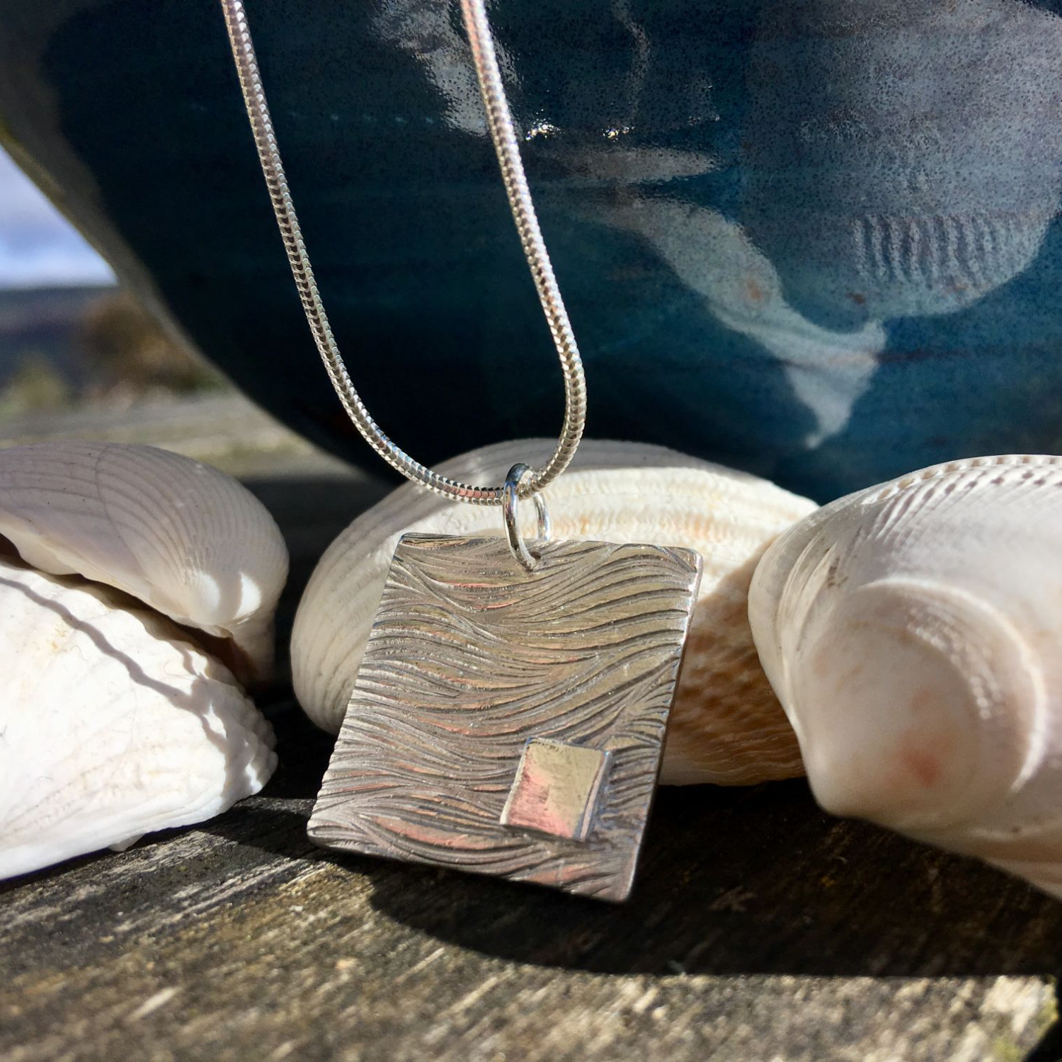 Seaside themed necklace sitting against shells