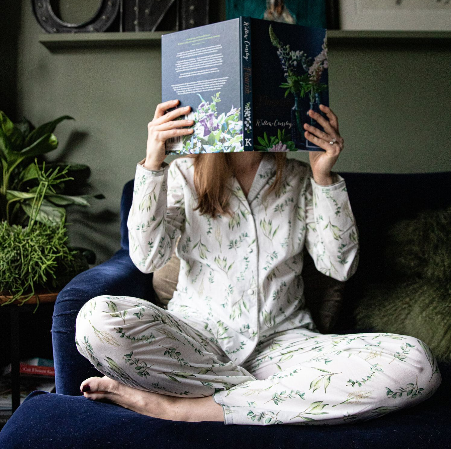 Woman wearing floral pyjamas reading a book