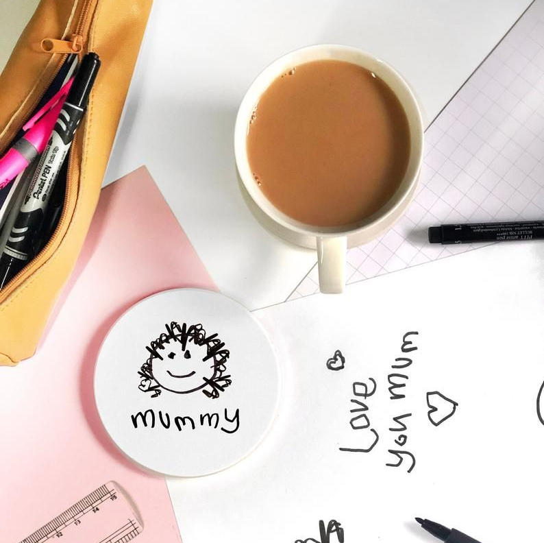 Personalised Coaster surrounded by drawings, stationary and coffee