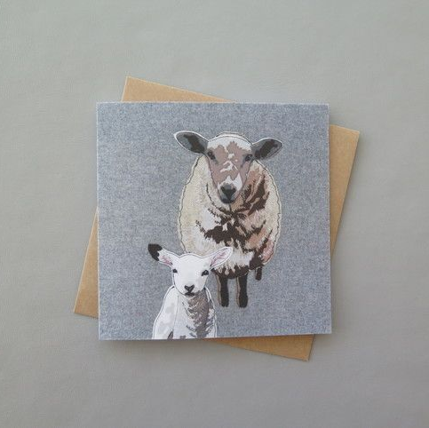 Card featuring a lamp and a sheep on a textured grey background