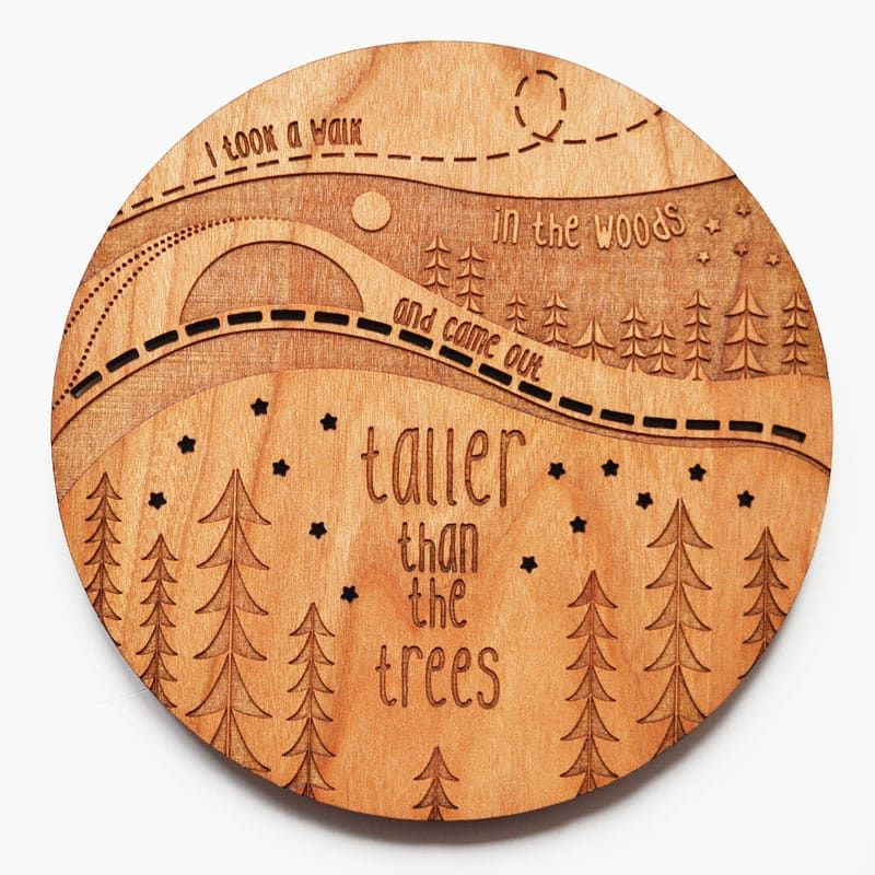 Engraved wooden coasters featuring trees and scenery