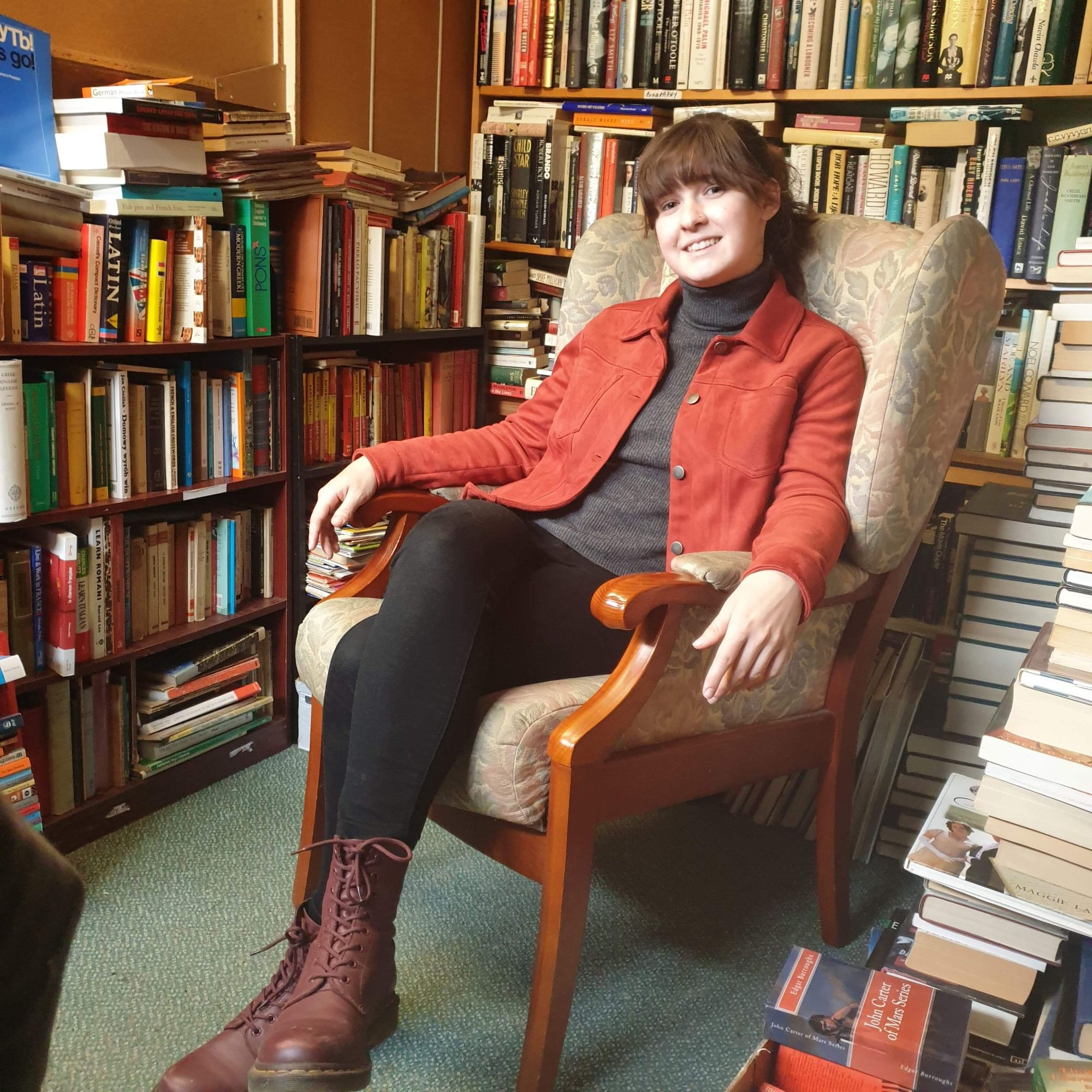 Rachel sits on an armchair surrounded by books