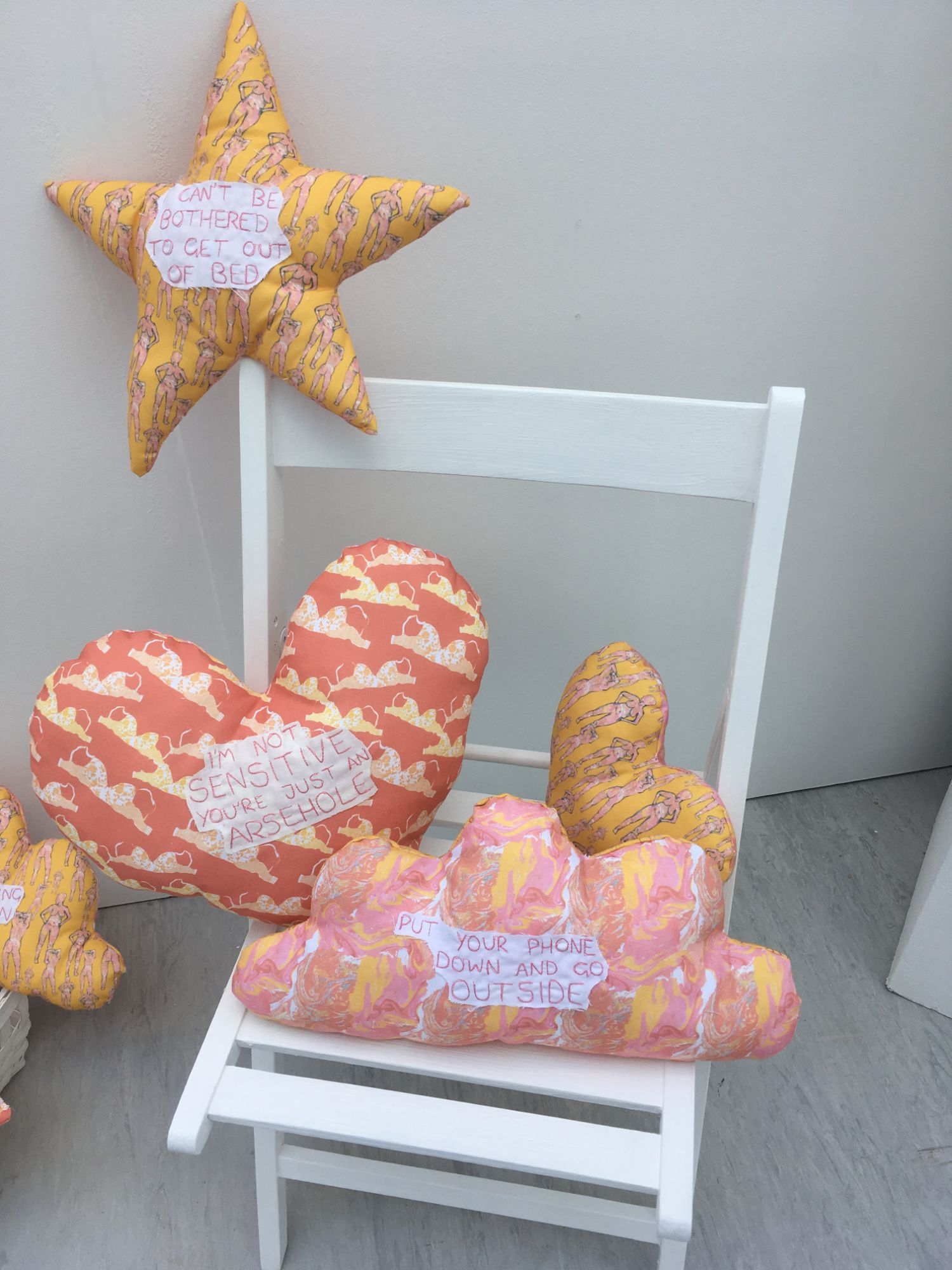 A selection of Contrary to Reason cushions on a white chair