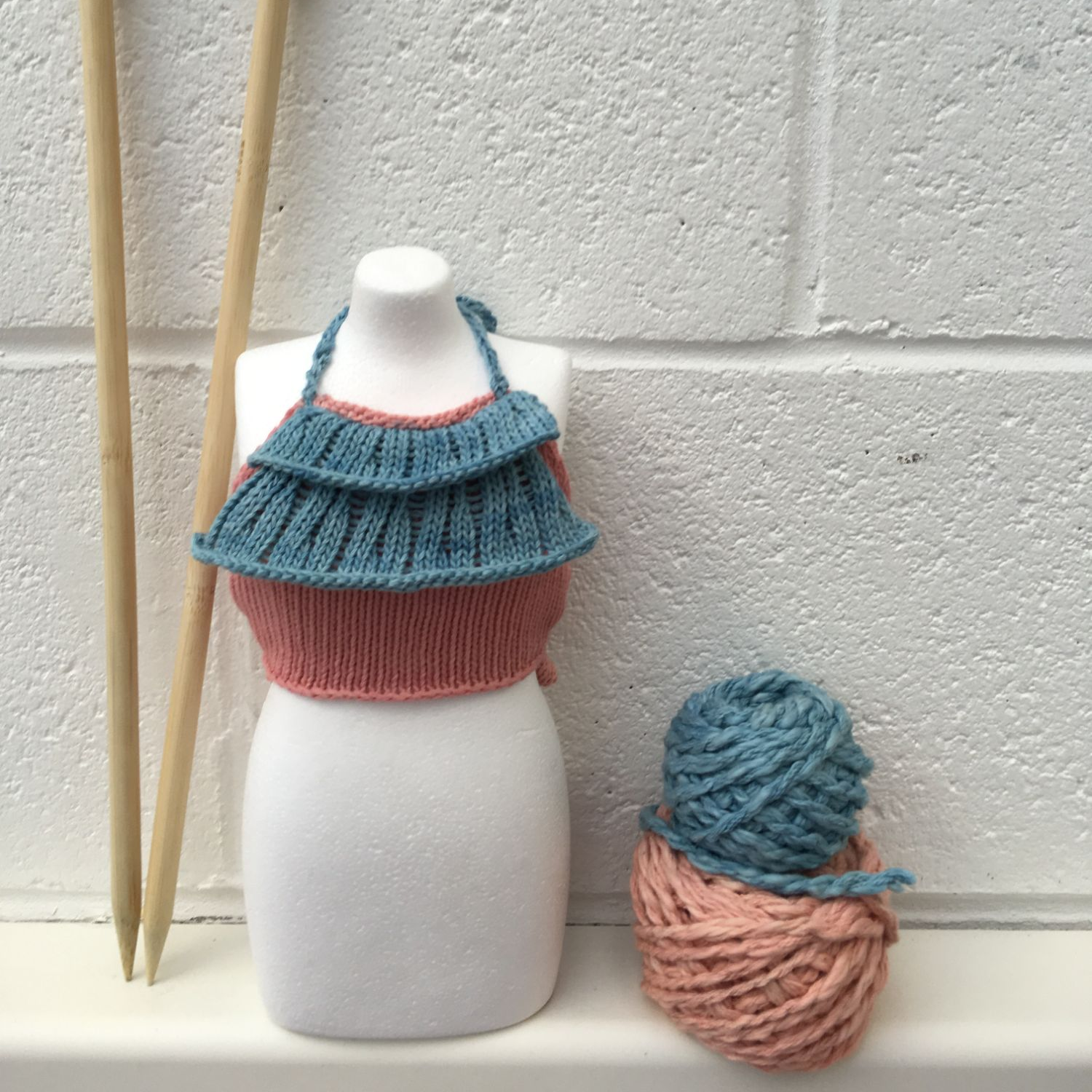 A cropped knit top on a mini mannequin with some pink and blue yarn samples beside it