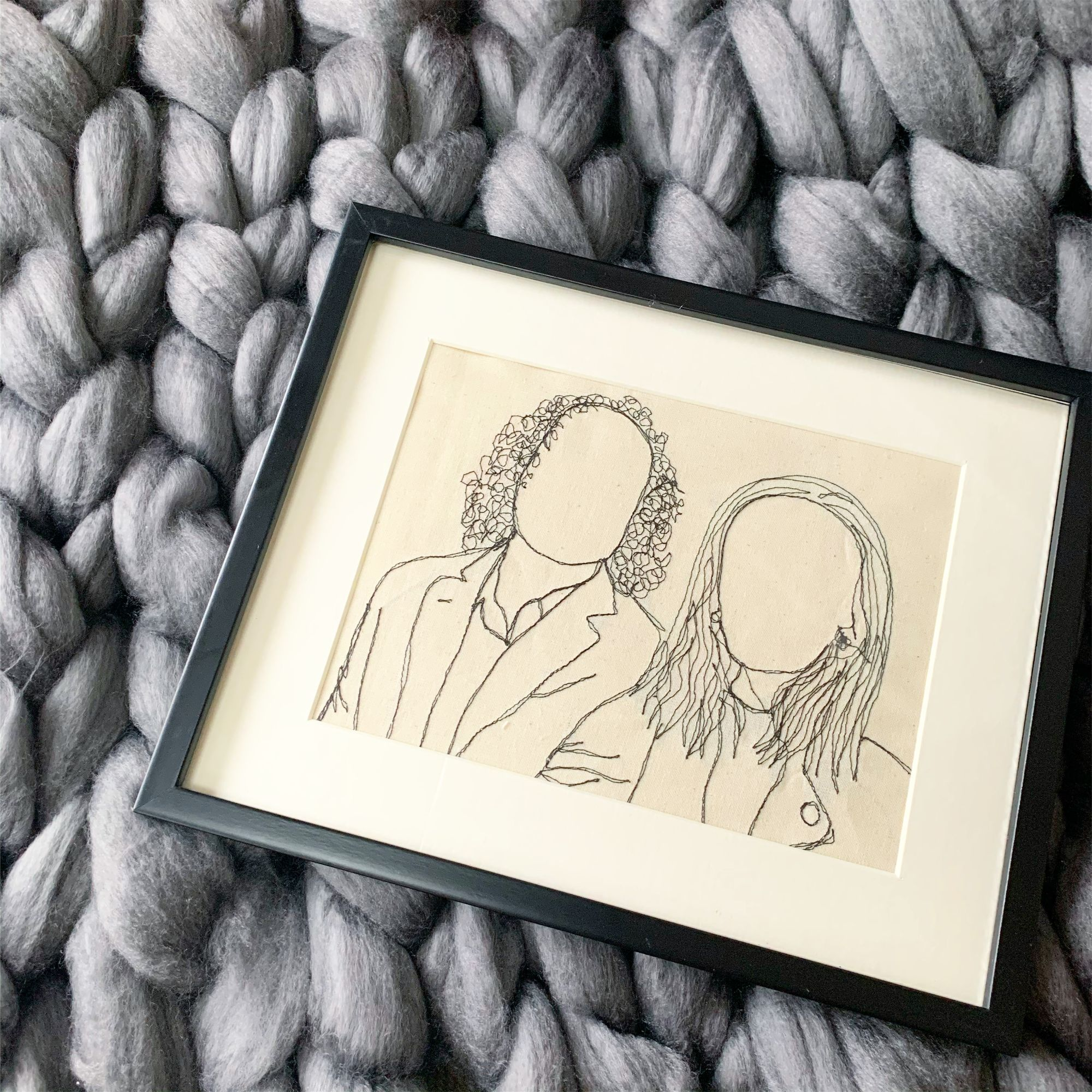 A machine stitched portrait of two people, framed and sitting on a chunky knitted backdrop