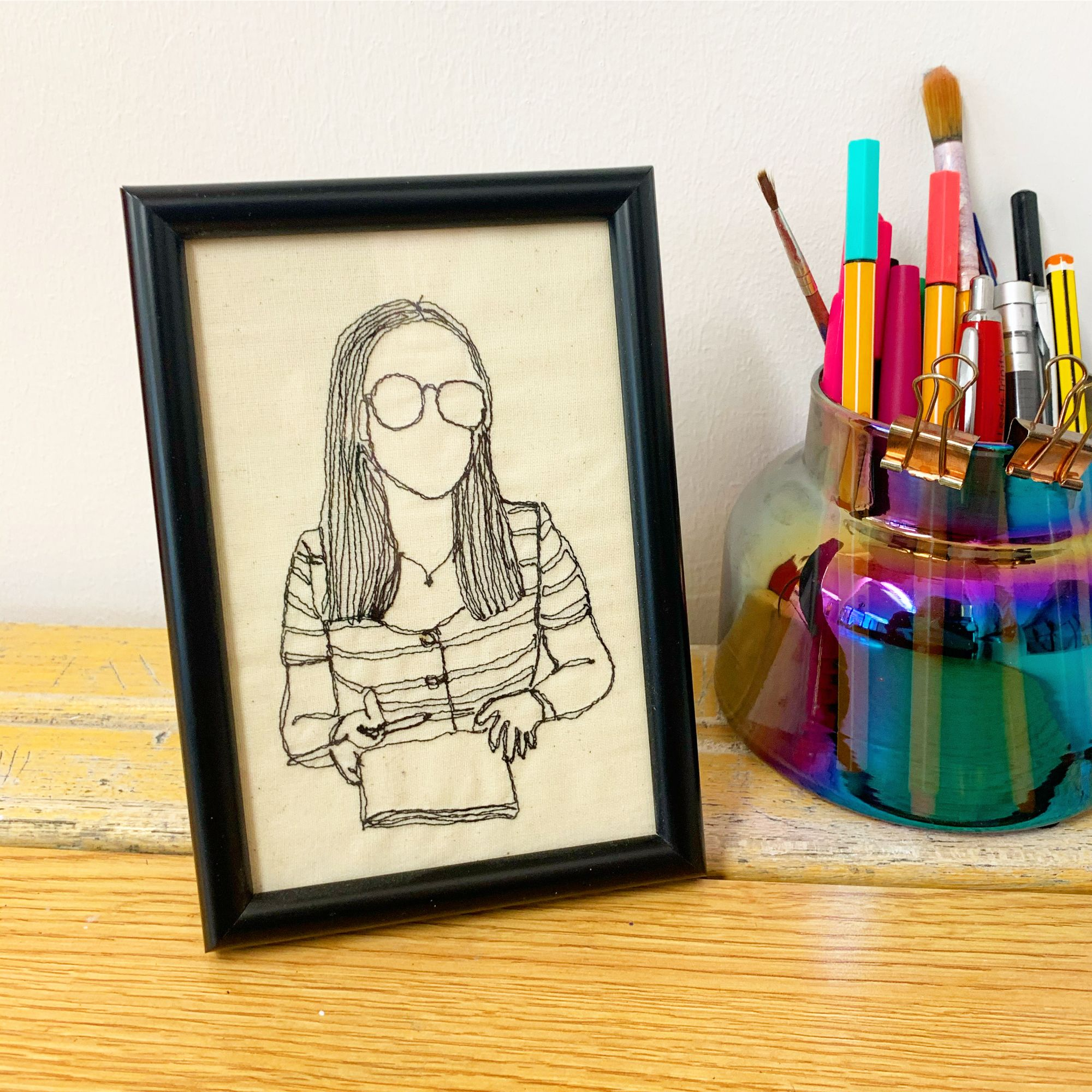 A machine stitched portraitof a young girl, framed and set on a desk next to a pen pot