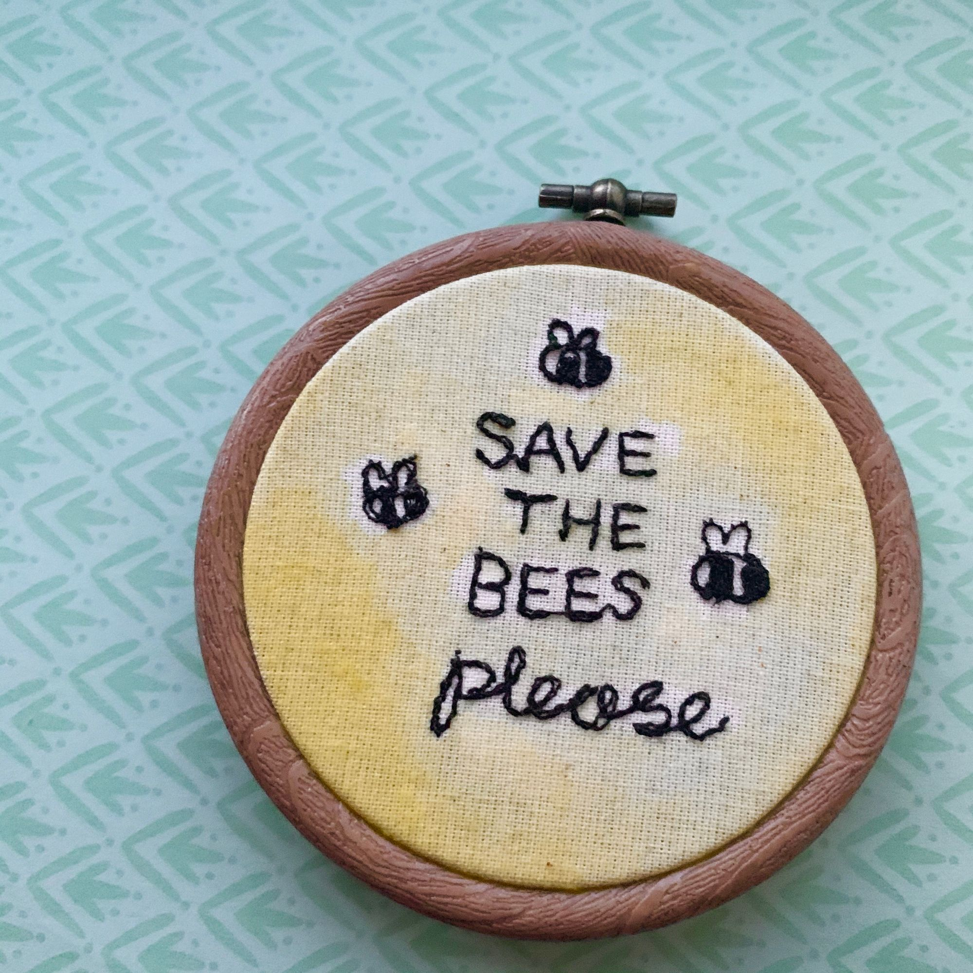A machine stitched piece reading 'save the bees please', in an embroidery hoop