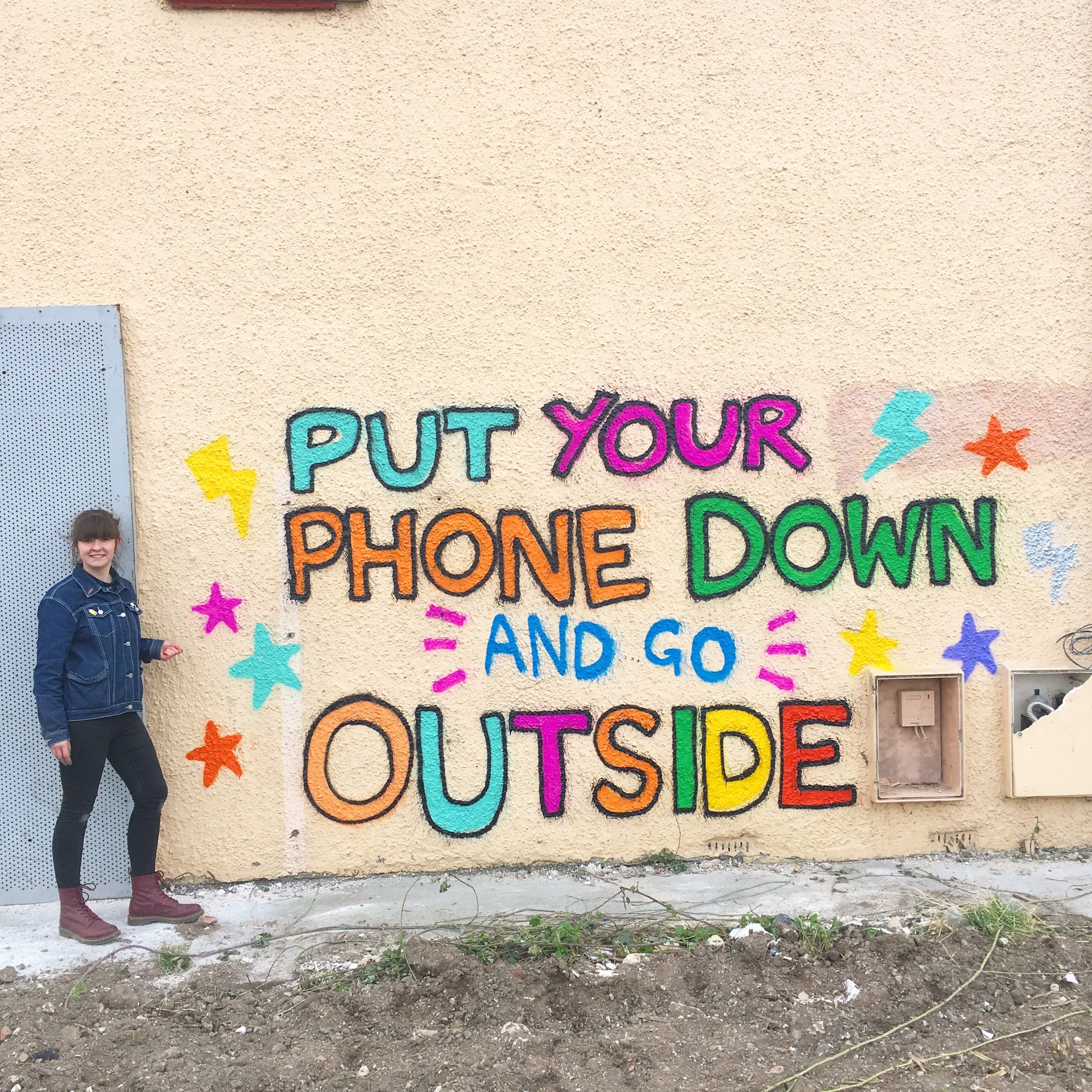 Painted graffiti on the side of a derelict house reading 'Put your phone down and Go Outside'