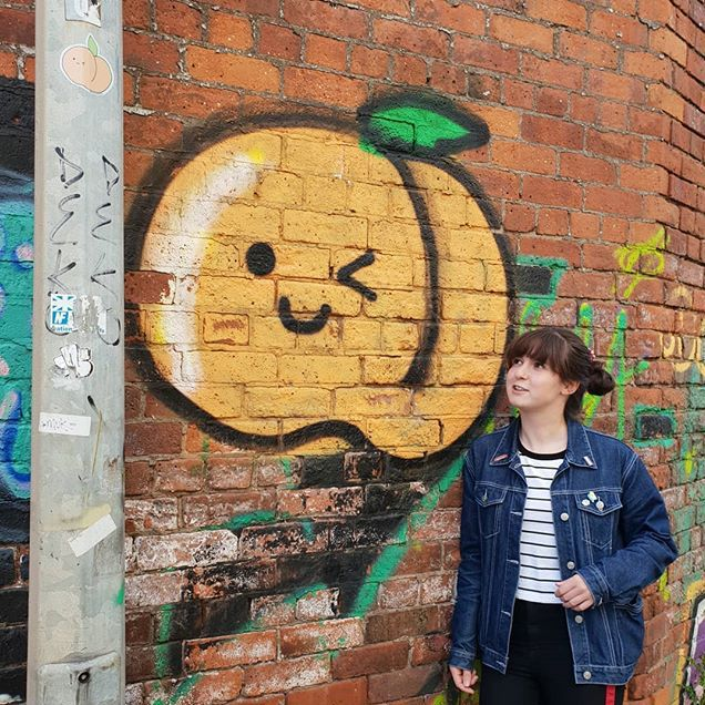 A winking cartoon peach on a brick wall