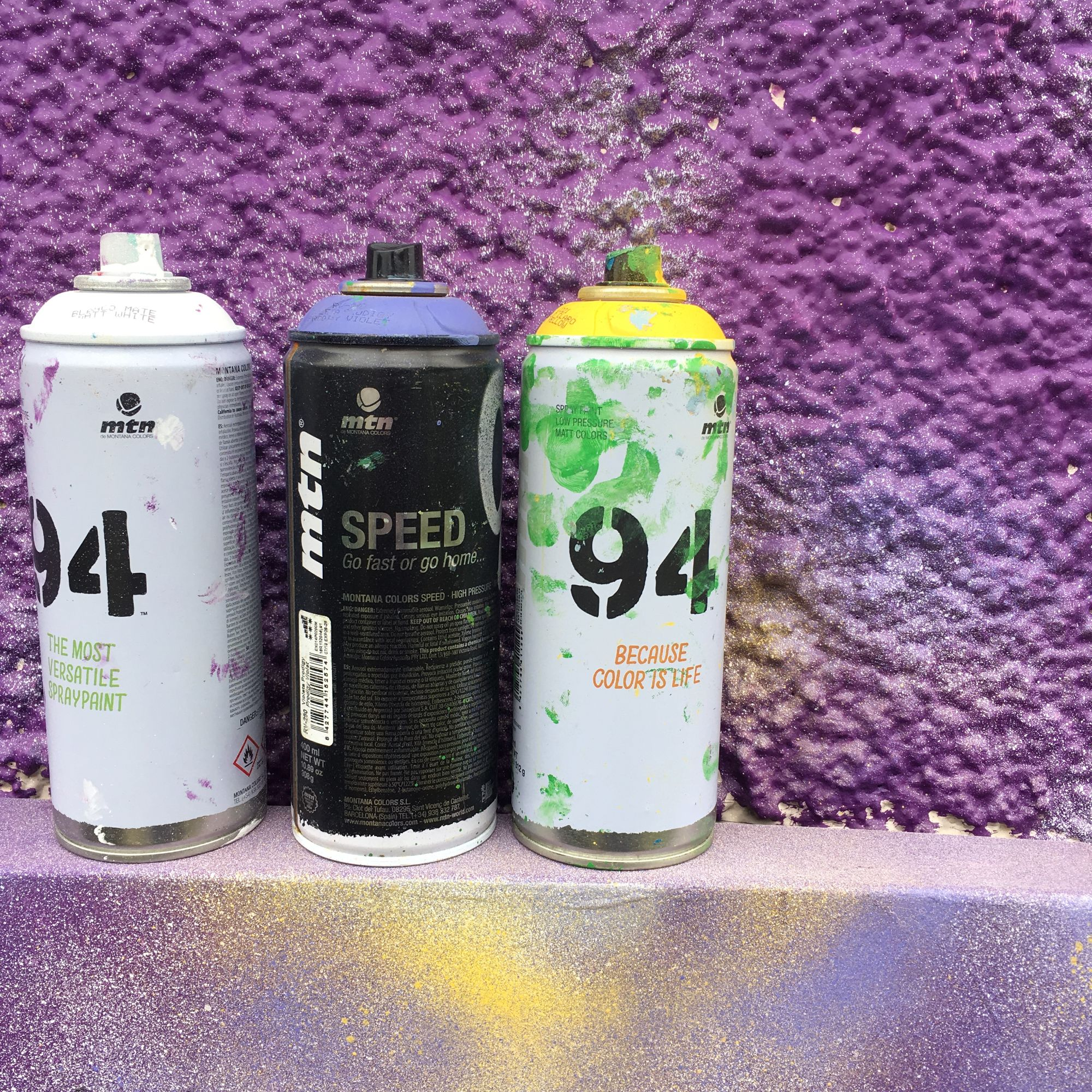 Tins of spray paint against a purple backdrop