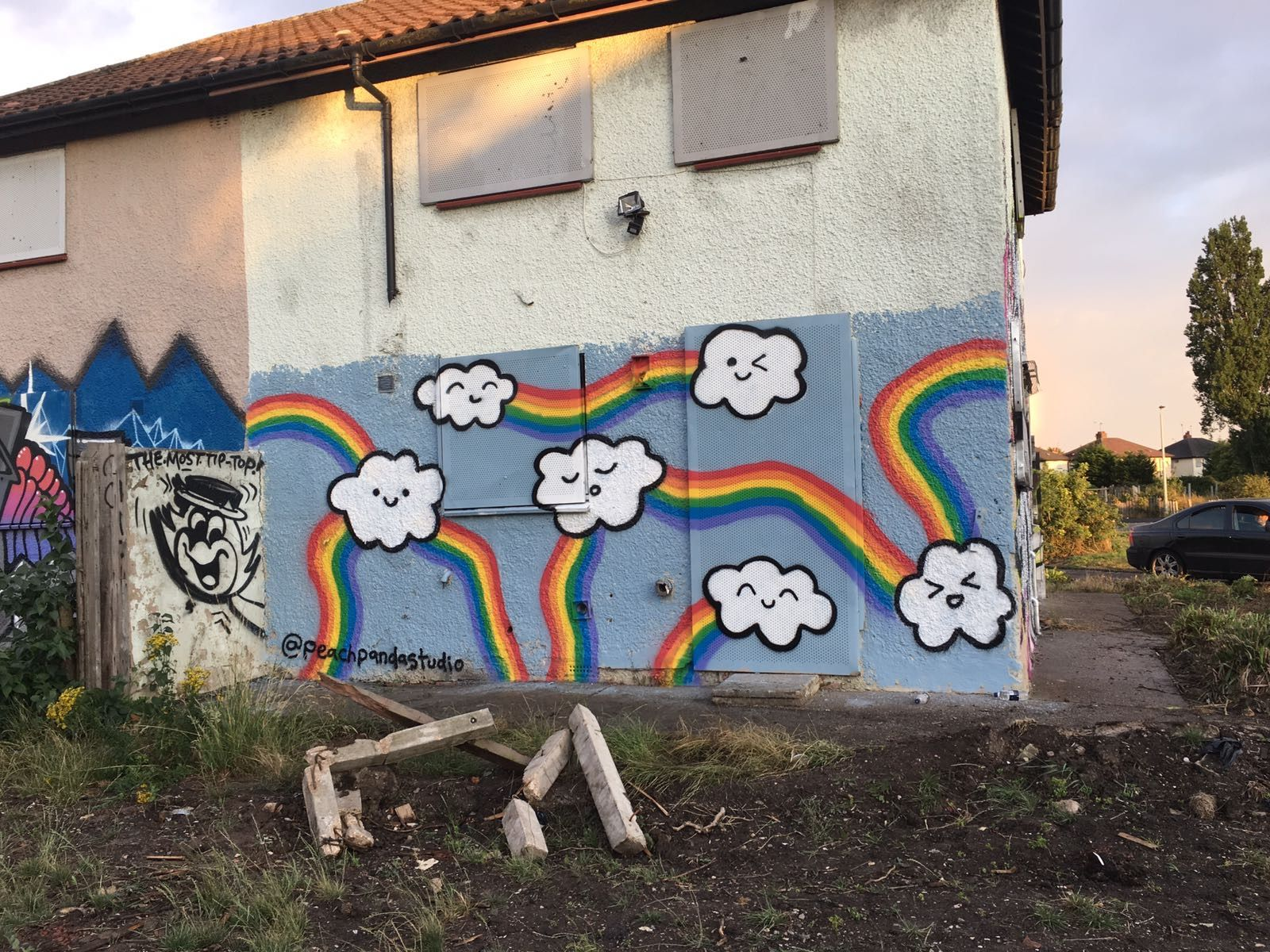 Painted rainbows and smiling clouds on the side of a derelict house