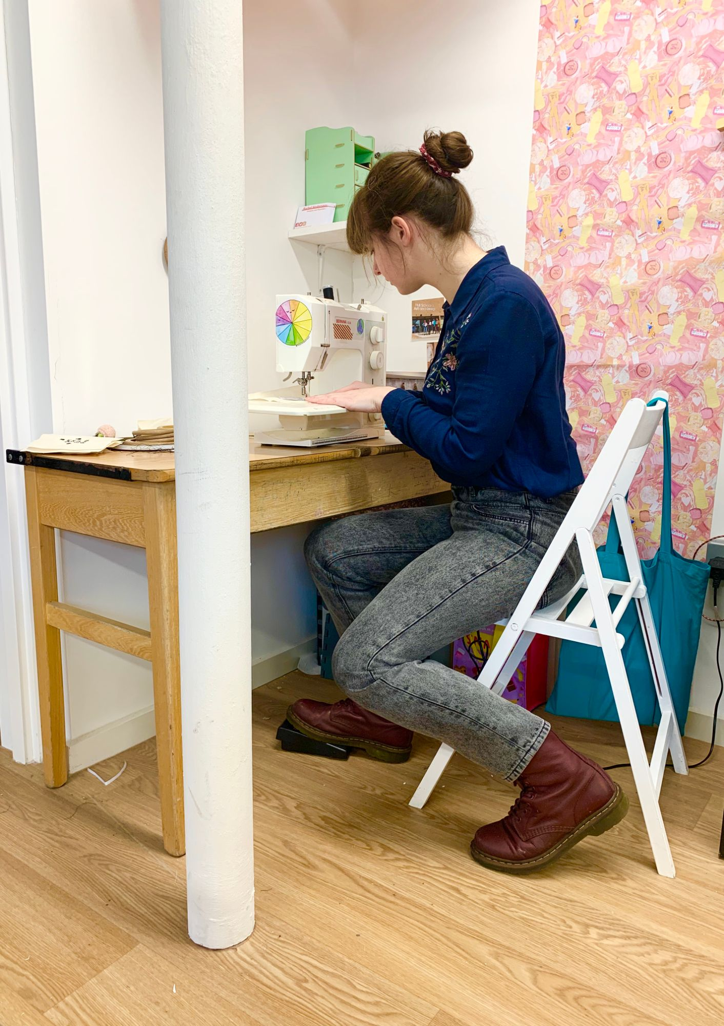 Rachel sat at her desk in her studio using a sewing machine