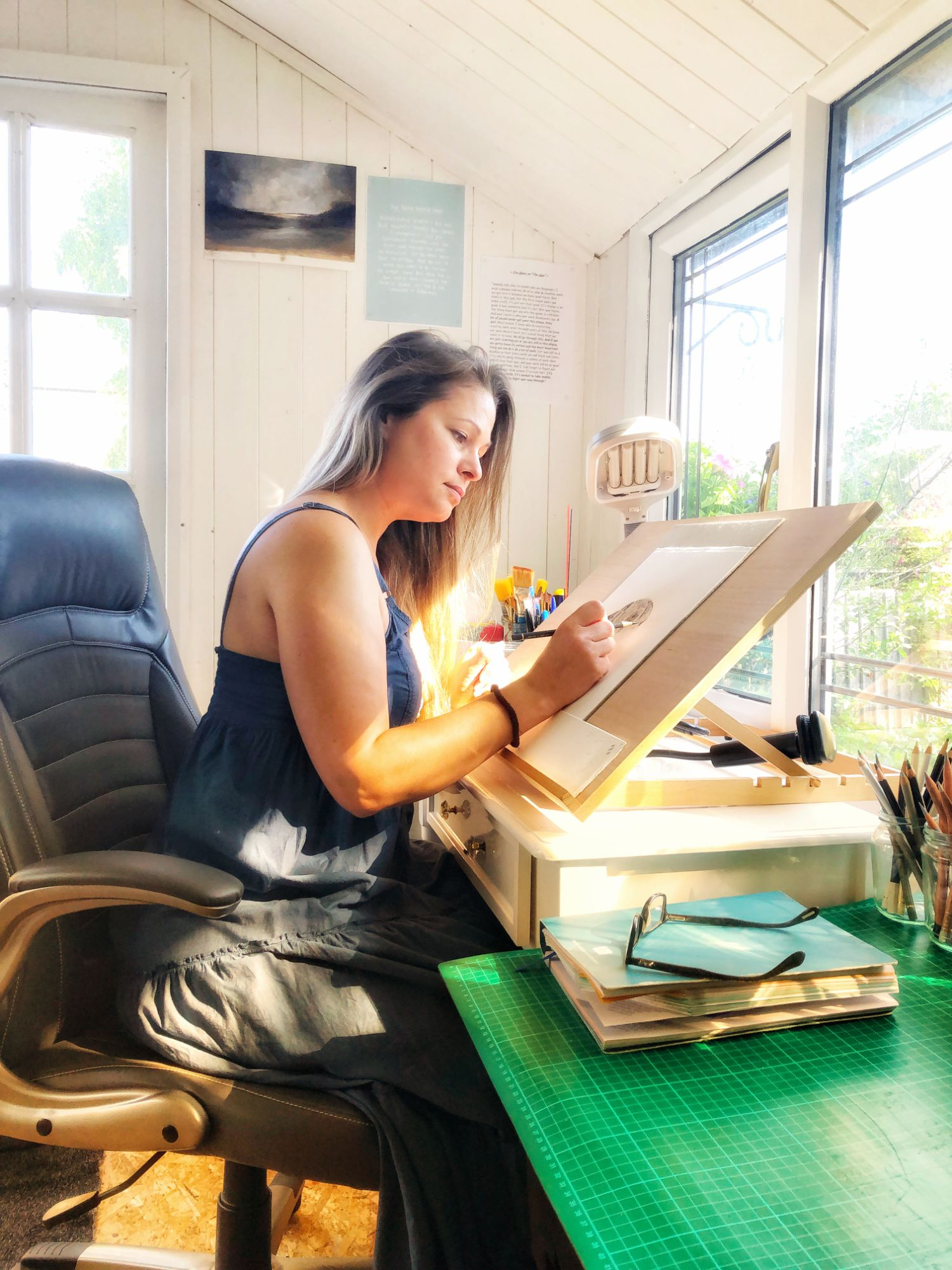 Carly drawing in her studio at the easel on the desk