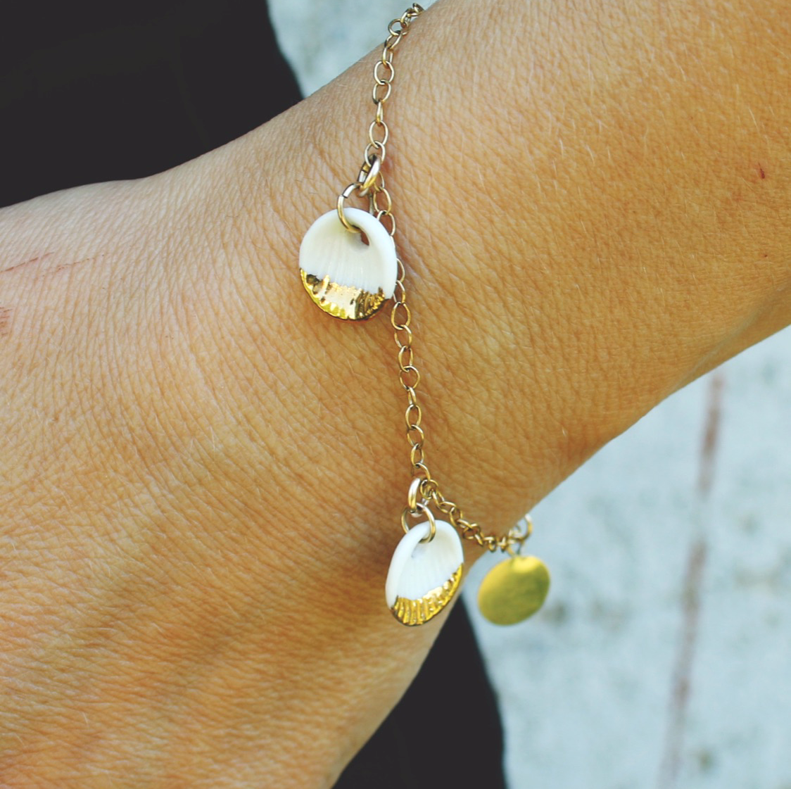 gold bracelet with white shells made of porcelain