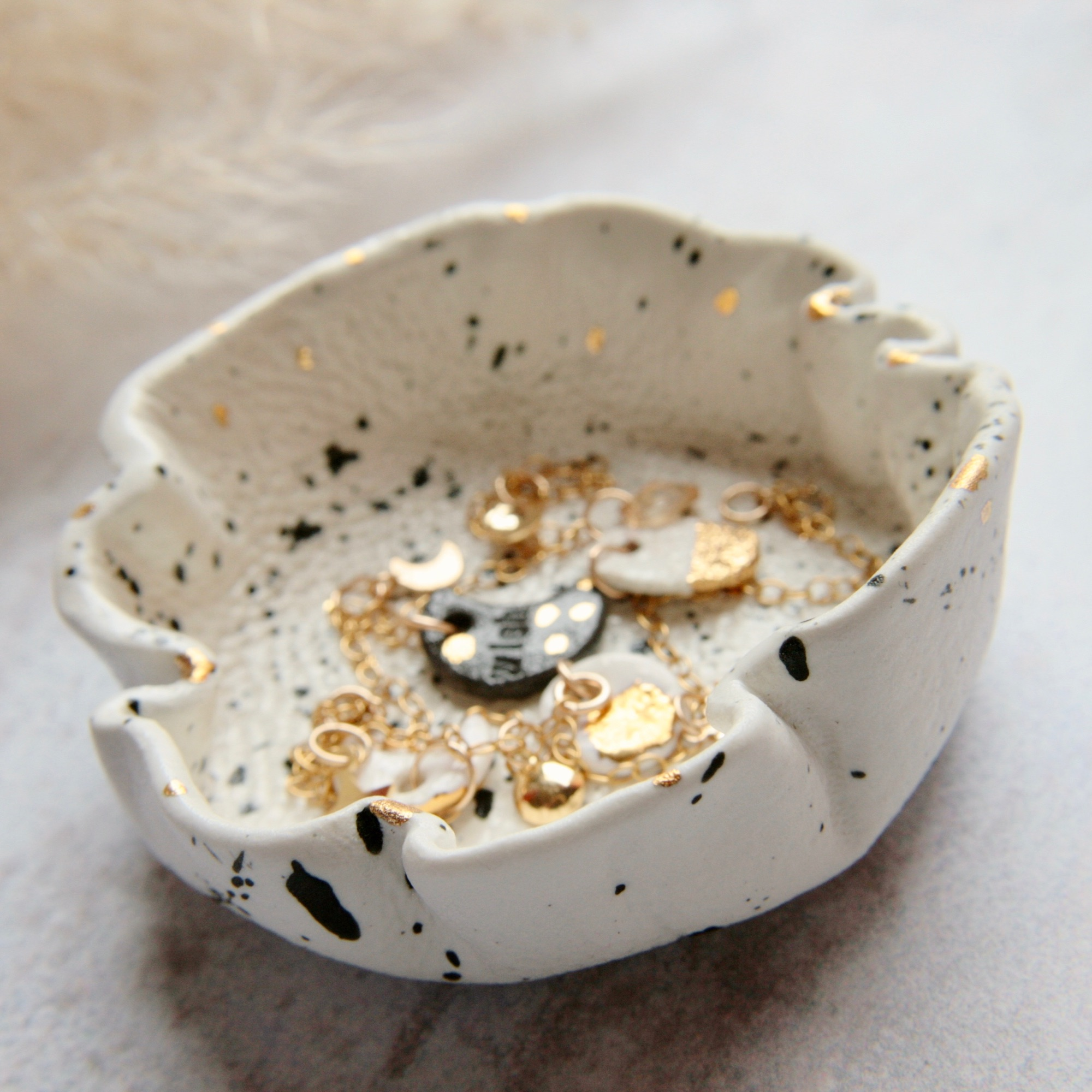 white ceramic dish splashed with black and gold  can be used as trinket or candle dish