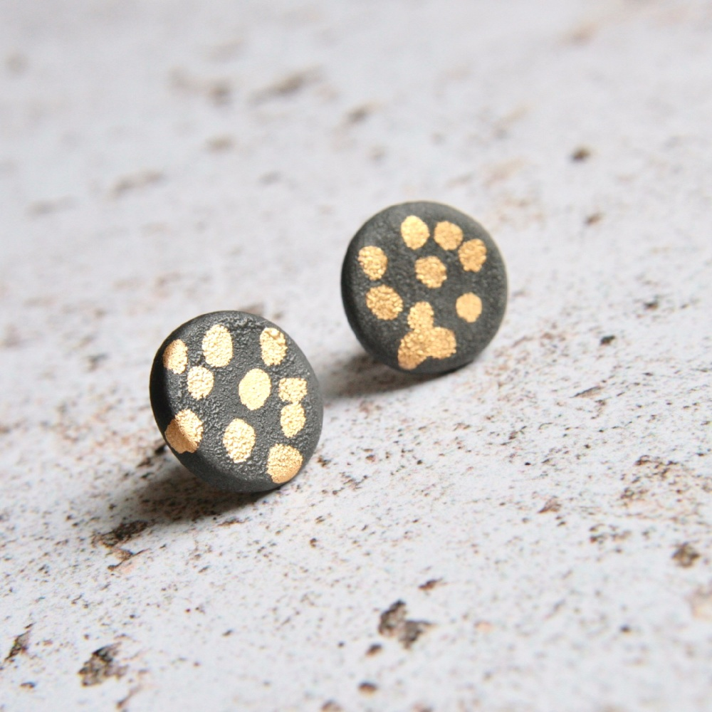Stud earrings with gold dots.