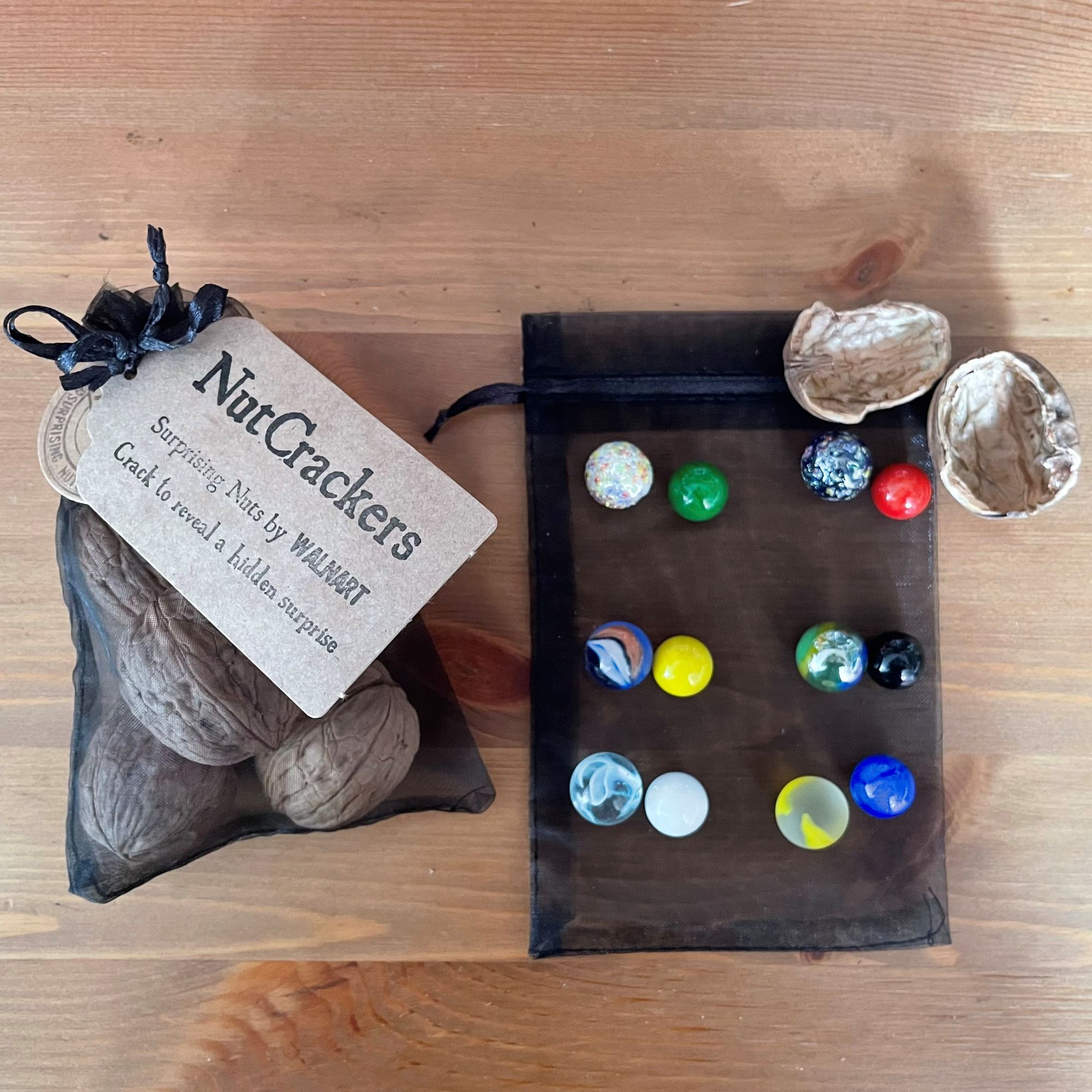 NutCrackers - Walnut shell surprise crackers with marbles in black organza bag contents.jpg