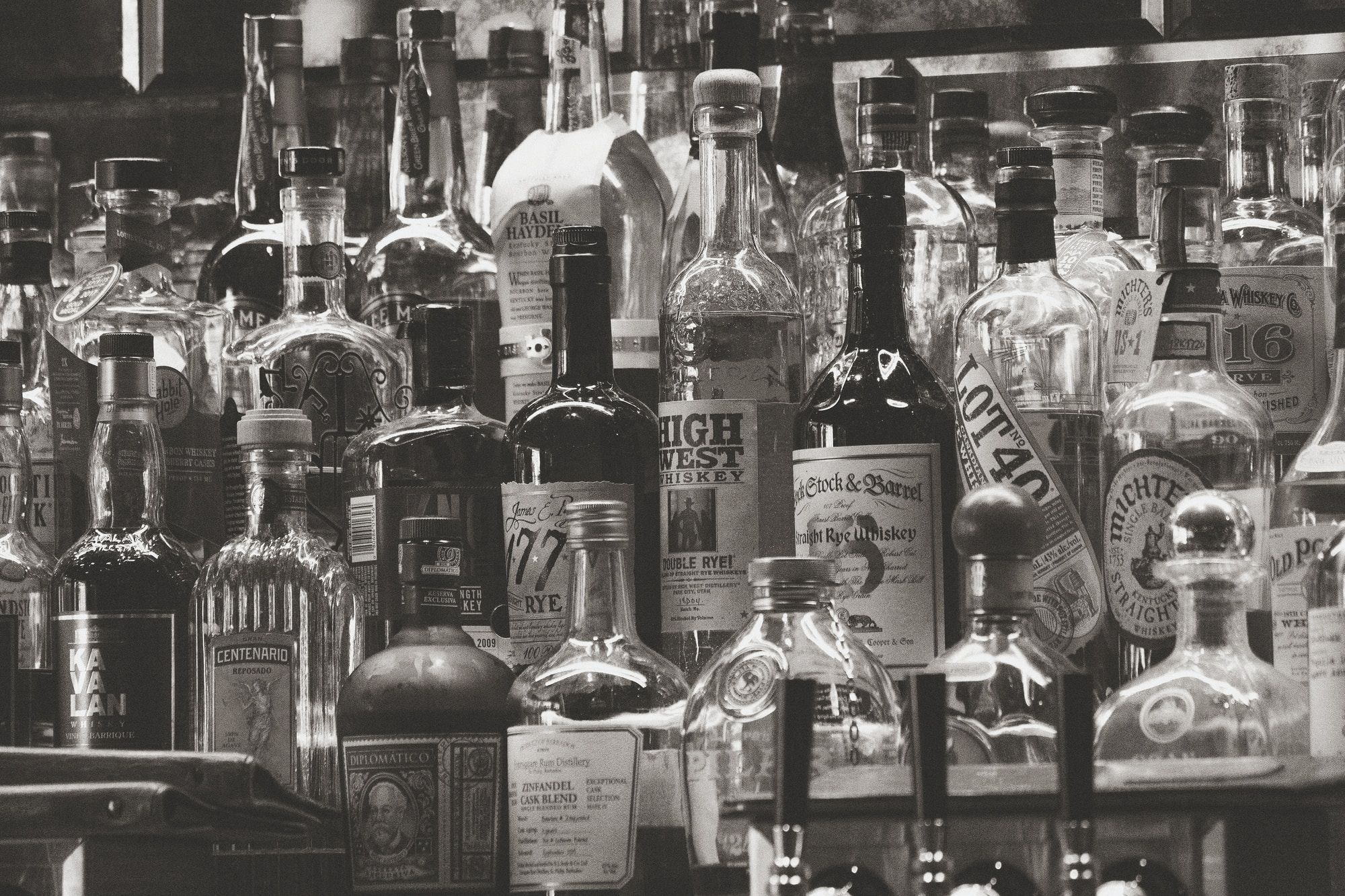 A wide selection of spirits displayed on a shelf within a bar.