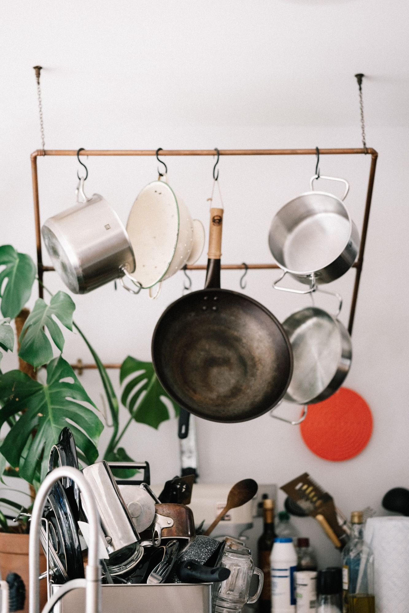Pots & pans hanging from a rack in a clean kitchen.
