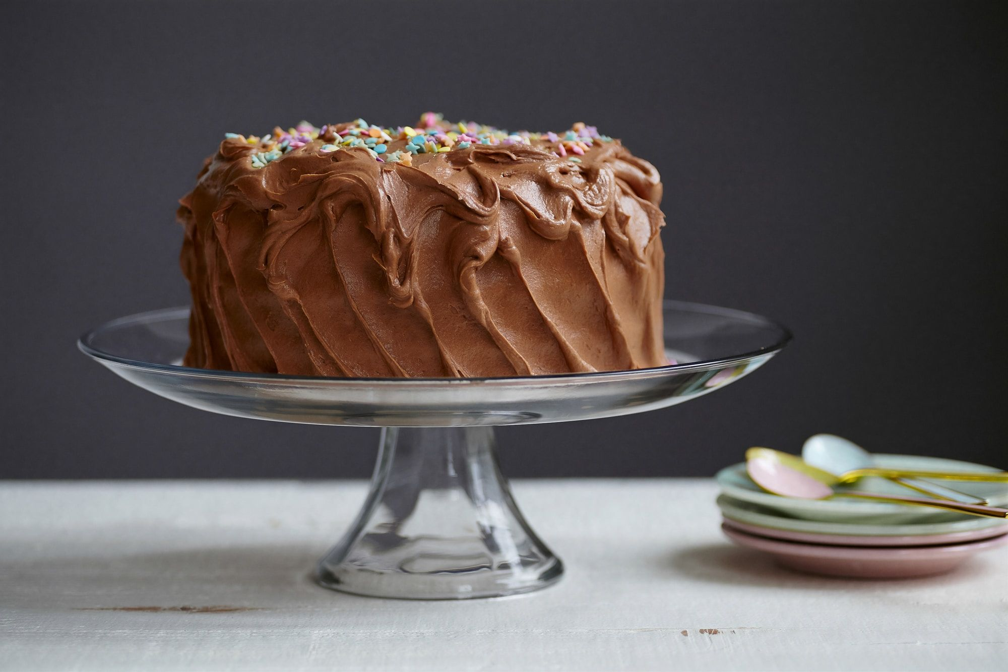 An indulgent chocolate cake situated on a glass stand