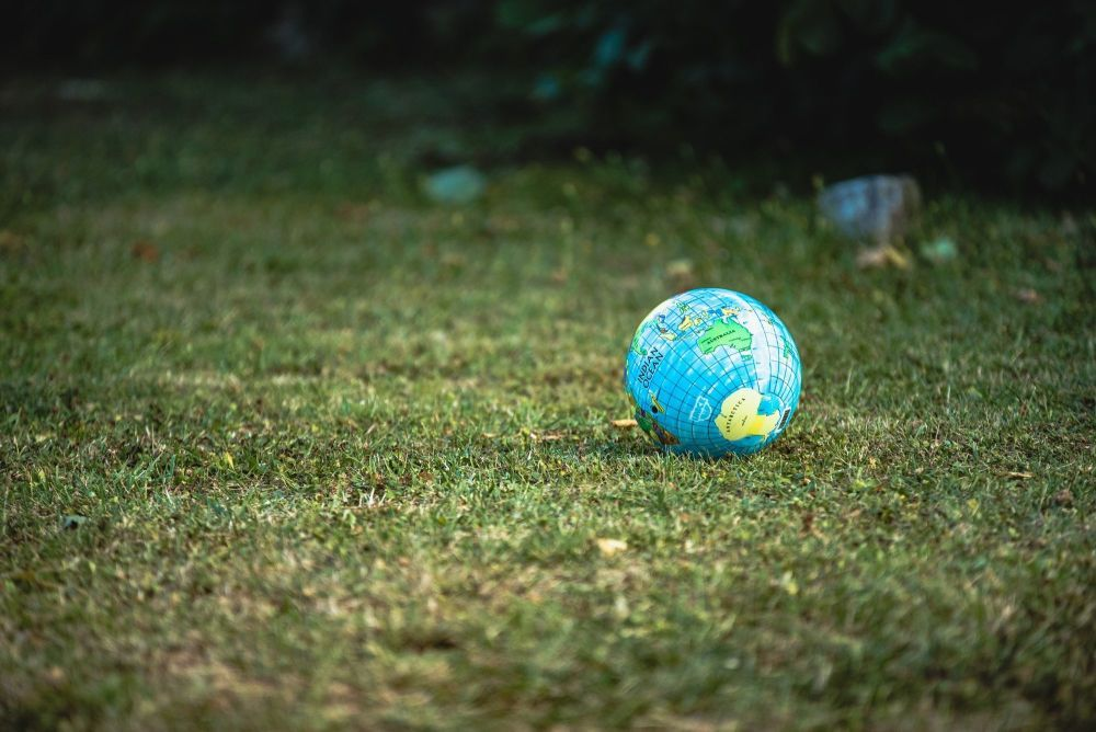 A globe of the world situated on grass