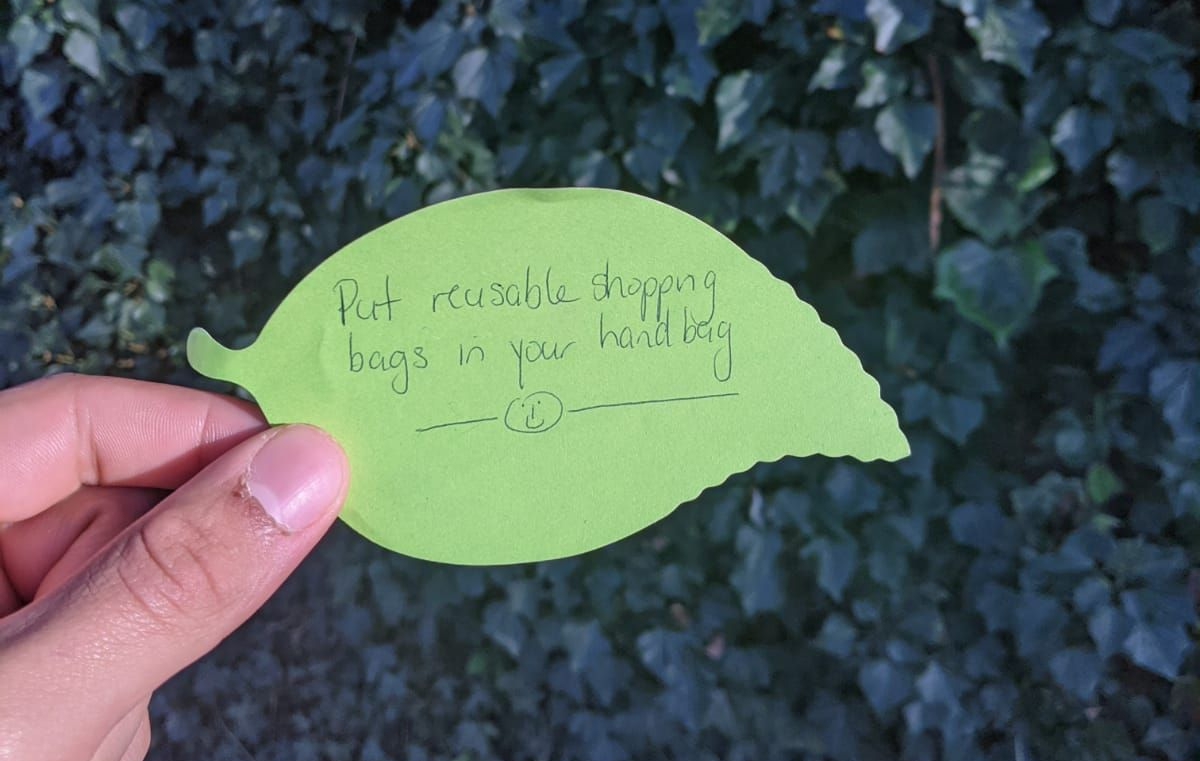 """A paper leaf with the writing """"Put reusable shopping bags in your hand bag"""""""