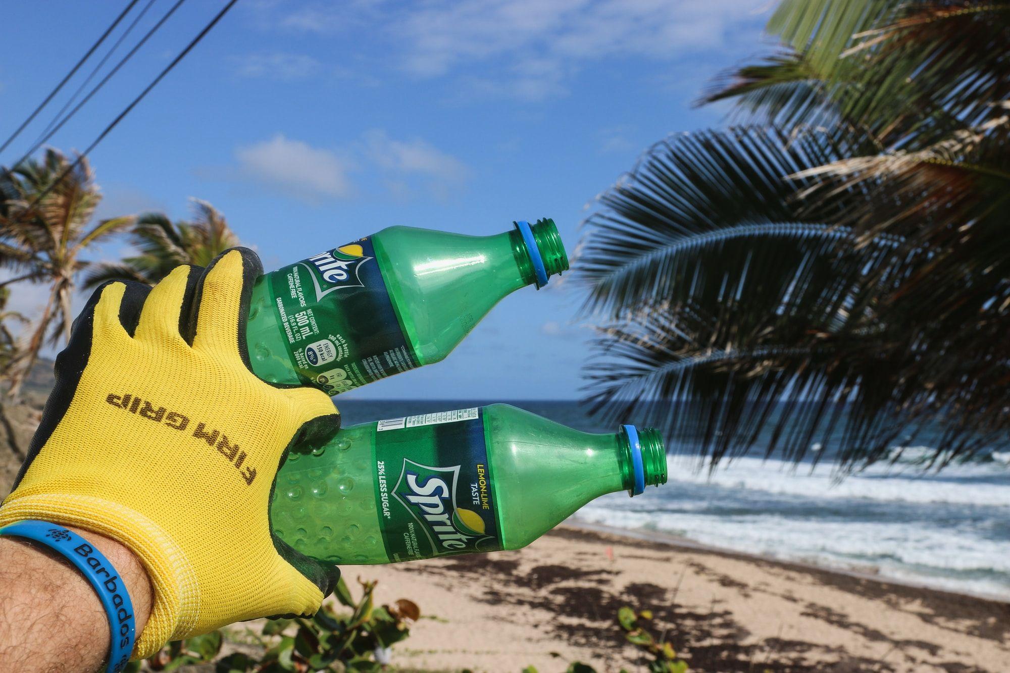 Beach Cleaner Picking Up 2 Plastic Sprite Bottles