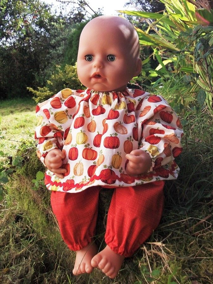 Doll wearing a patterned top and orange trousers