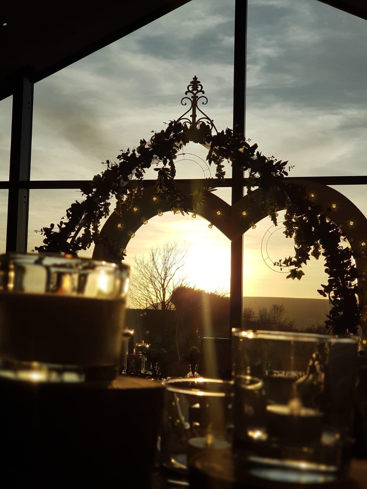 Love Heart Arch and Floral Arch in Front of Windows at Sunset