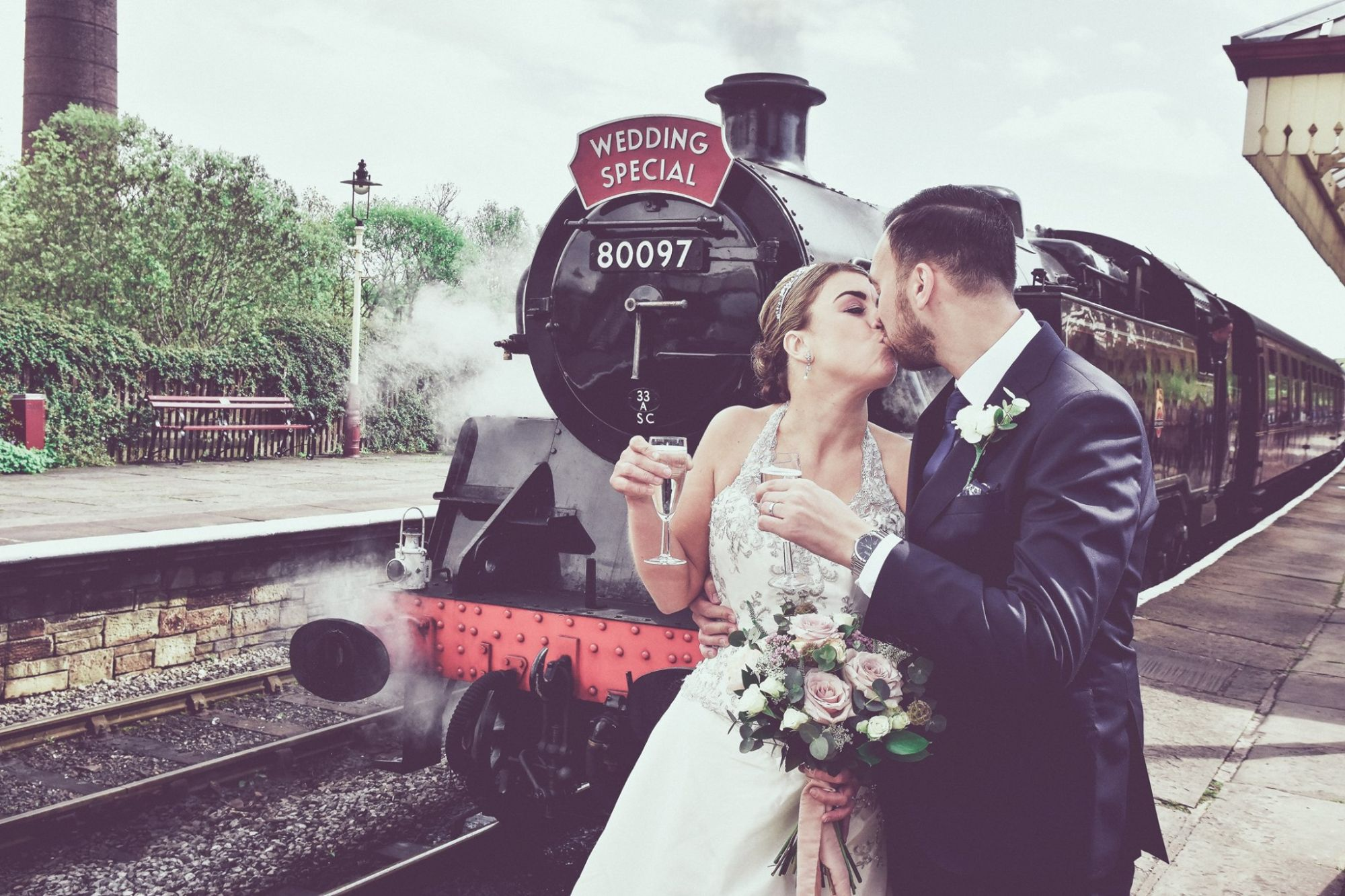 Intimate photograph of a Bride and Groom at Ramsbottom Railway with the Steam Train in the Background
