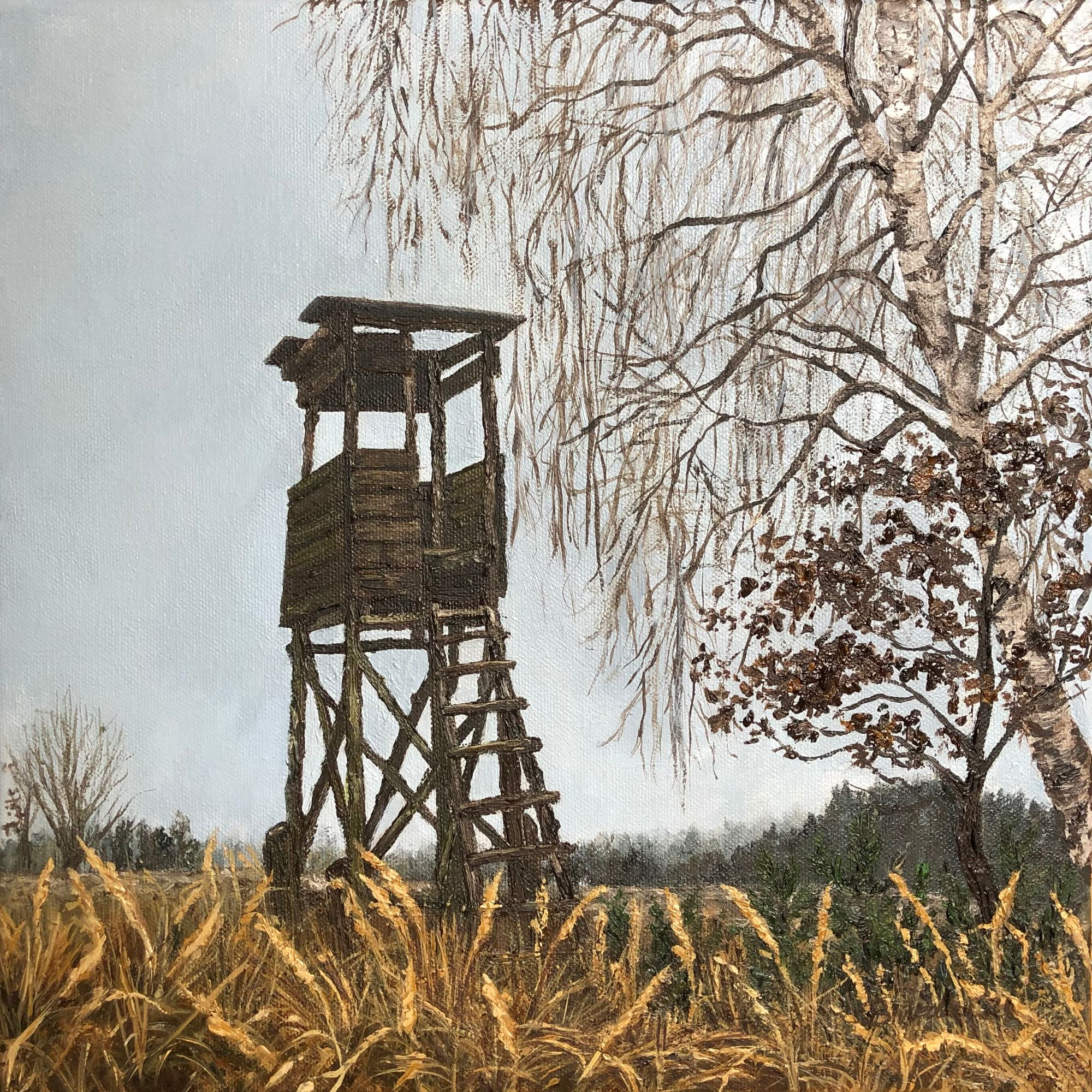 Hunting tower in January landscape with yellow grasses and a bare birch tree beside it.