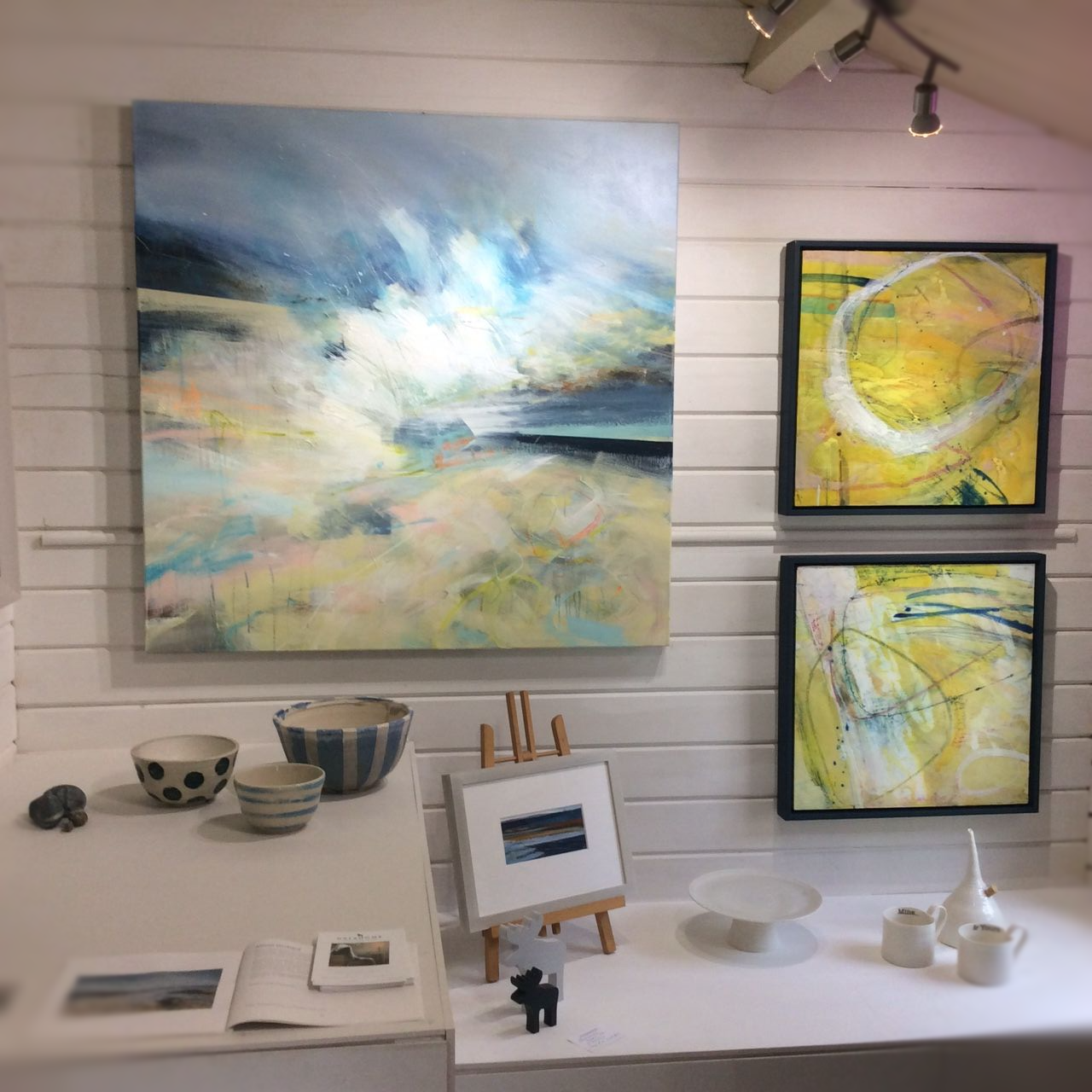 gallery wall with yellow abstract encaustic paintings and large seascape
