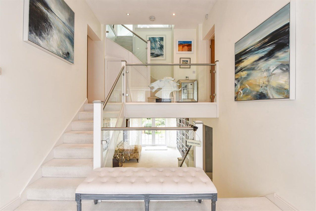 interior of minimalist hallway with two large abstract seascape paintings