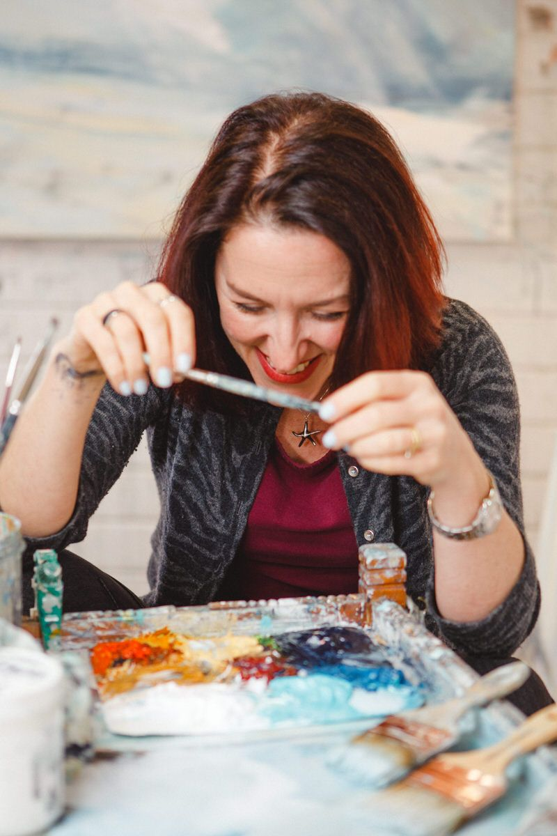 Alison laughing holding paintbrush in front of palette of colours