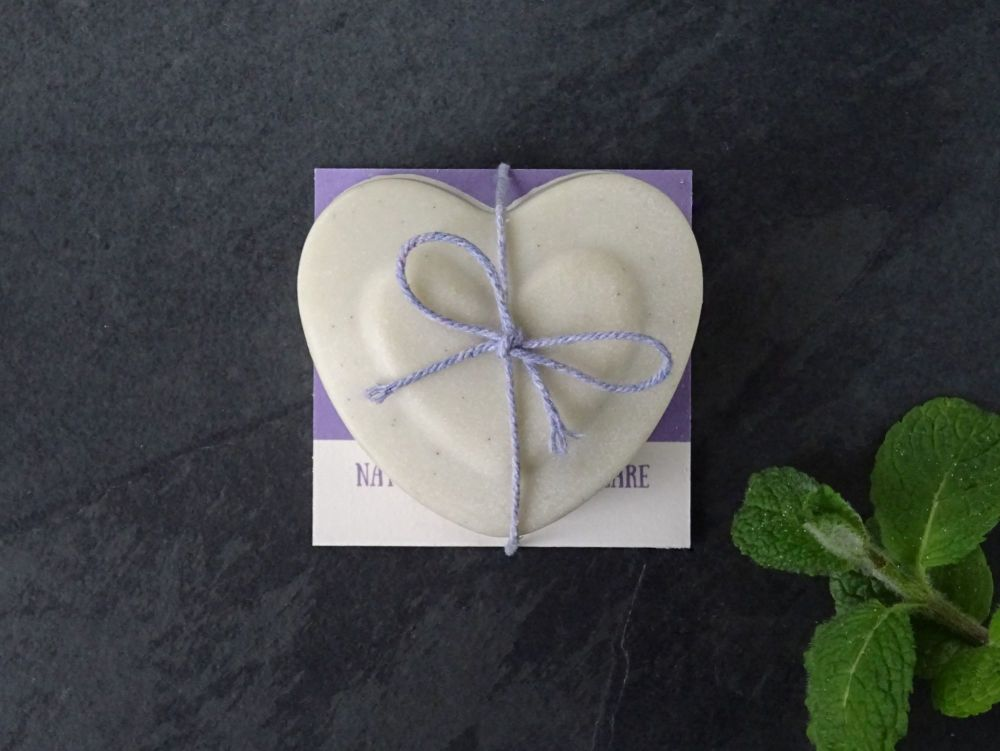 Pale grey heart shaped handmade soap on square label tied atop laid on slat