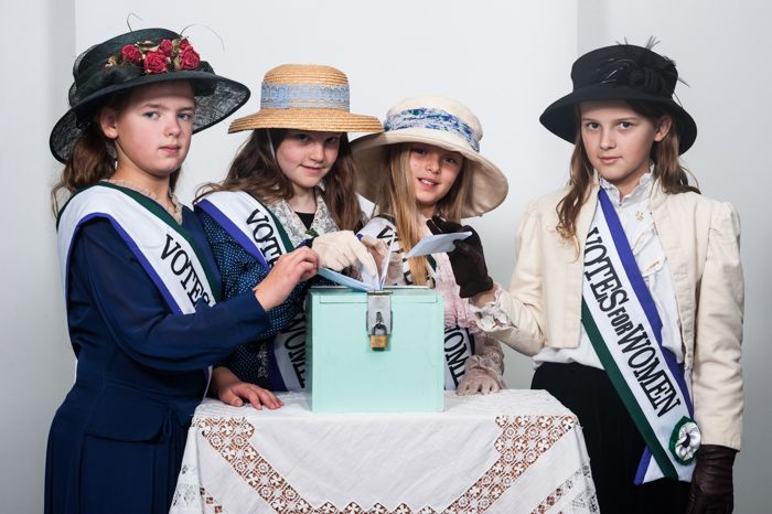 4 female pupils from Patcham Junior School  pose in costume as suffragettes and wearing 'Votes for Women' sashes made in Gladrags sewing workshop.