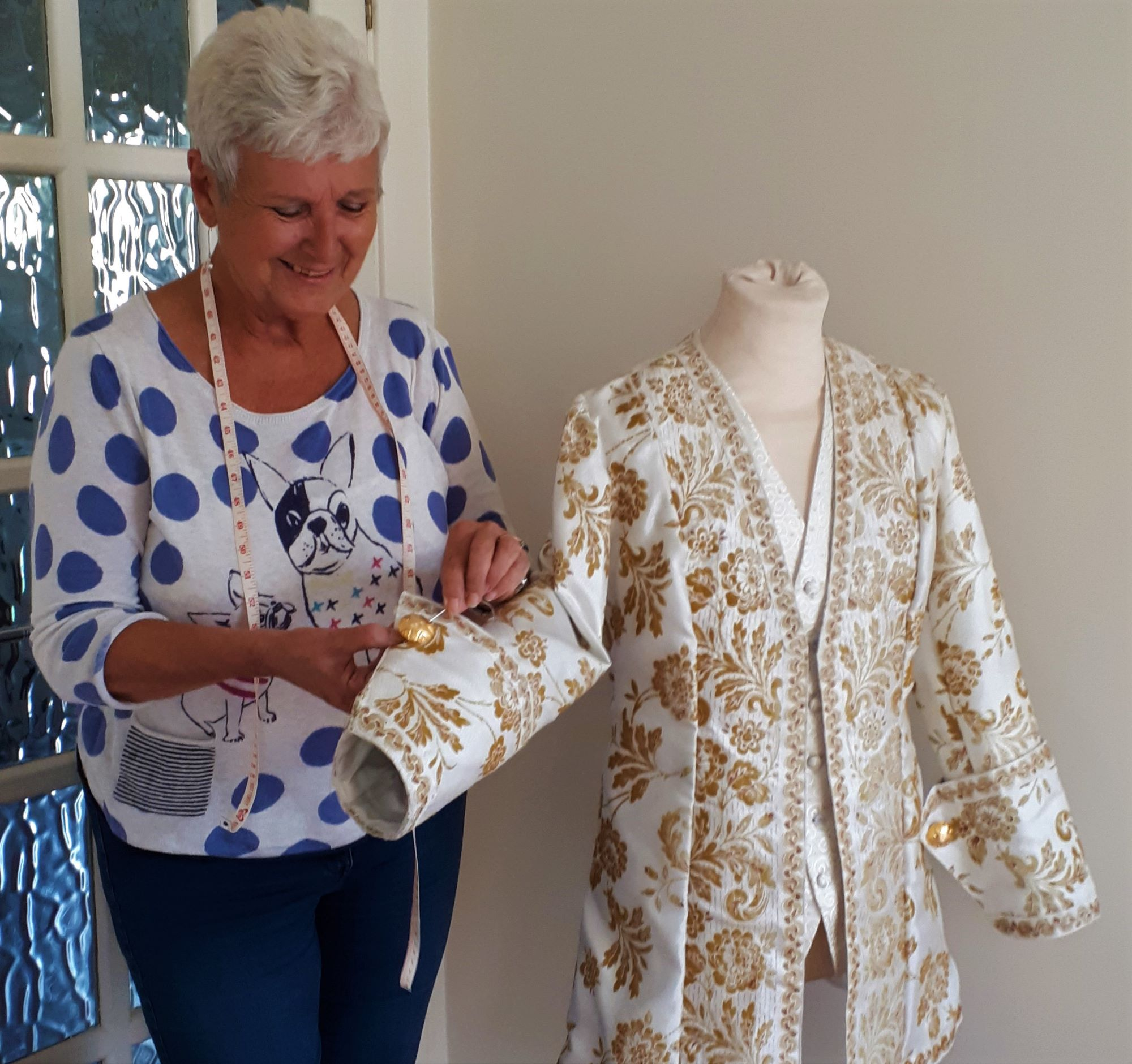 Marilyn secures her last stitch in a jacket   she made from recycled fabric, trimmings and buttons.