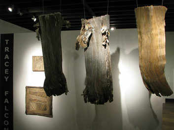 Exhibition view of newspaper artwork by Tracey Falcon. Hanging, flayed, newspaper trunks.